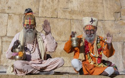 two hindu sadhus sitting with their backs against a wall, holding their malas with bright yellow stripes drawn on their foreheads with vermilion