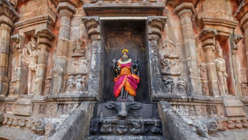 Beautiful Goddess Durga statue with bright orange and pink saree on a temple walll