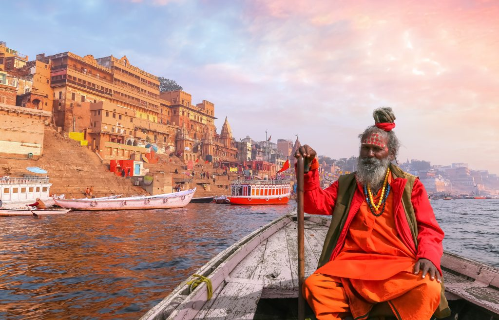 Sadhu on a boat in the river Ganges with the historical city of Varanasi in the backdrop