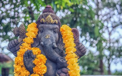 Grey Ganesha statue wearing a bright yellow garland and an Om on the trunk and green trees in the background