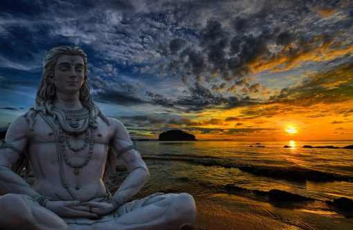Lord Shiva statue in meditation pose on the banks of river Ganga during a beautiful sunset with dramatic clouds above